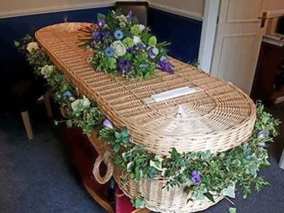 Garland and hand tied sheath on a wicker coffin